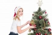Fotografie Seitenansicht der lächelnde Frau in Santa Claus Hut dekorieren Weihnachtsbaum isoliert auf weiss
