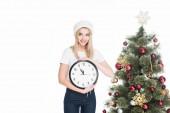 Fényképek santa claus kalap tartja az órát közel karácsonyfa elszigetelt fehér fiatal nő portréja
