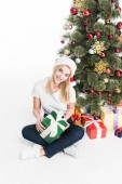 high angle view of smiling woman in santa claus hat with wrapped gift sitting near christmas tree isolated on white