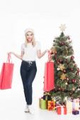 Fényképek santa claus kalap fiatal nő kezében elszigetelt fehér karácsonyfa közelében bevásárló táskák