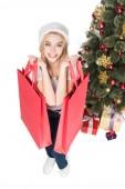 Fényképek magas, szög, Kilátás mosolygó nő a bevásárló szatyrok elszigetelt fehér karácsonyfa közelében santa claus kalap