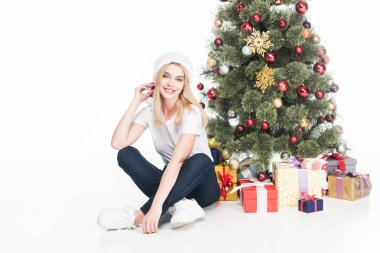 cheerful young woman in santa claus hat sitting near christmas tree isolated on white