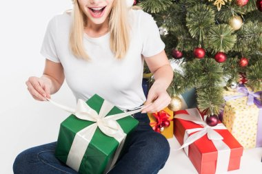 partial view of emotional woman with wrapped gift sitting near christmas tree isolated on white
