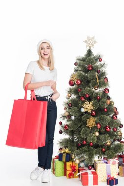 young woman in santa claus hat with shopping bags near christmas tree isolated on white
