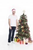 Fényképek santa claus kalap állandó elszigetelt fehér karácsonyfa közelében fiatalember
