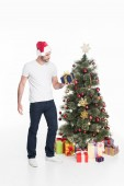 Fotografie young man in santa claus hat with wrapped present standing at christmas tree isolated on white