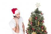 Fényképek santa claus kalap beszélő smartphone közelében karácsonyfa elszigetelt fehér ember