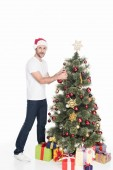 young man in red santa claus hat decorating christmas tree isolated on white