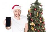 muž v santa claus klobouk znázorňující smartphone s prázdnou obrazovku poblíž vánoční stromeček izolované na bílém