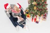 santa claus kalap laptop közelében karácsonyfa elszigetelt fehér pár felülnézete