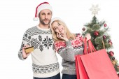 Fotografie mladý pár v svetry a čepice santa claus s nákupní tašky a kreditní kartu u vánočního stromu izolované na bílém