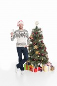 man in sweater and santa claus hat with glass of champagne standing near christmas tree isolated on white
