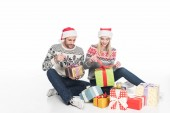 couple in sweaters and santa claus hats unwrapping presents while sitting on floor isolated on white