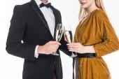 Fotografia vista parziale di vetri clinking delle coppie alla moda di champagne isolato su bianco