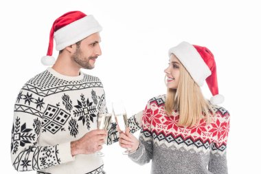 couple in sweaters and santa claus hats clinking glasses of champagne isolated on white