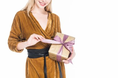 partial view of smiling woman with wrapped gift in hands isolated on white