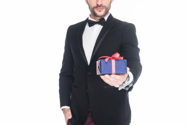 cropped shot of man in stylish suit holding wrapped present isolated on white