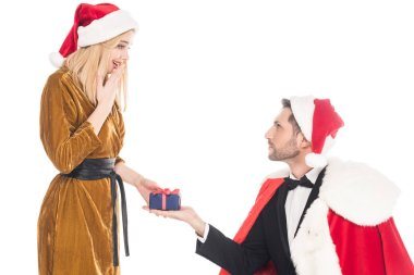 man in santa claus costume presenting gift to surprised girlfriend in santa claus hat isolated on white