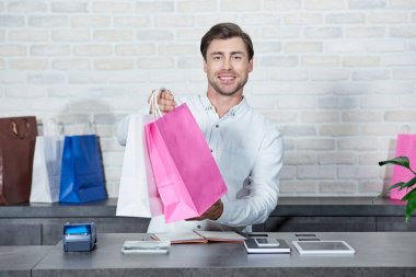Handsome young salesman holding shopping bags and smiling at camera in store stock vector