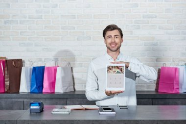 Handsome young salesman holding digital tablet with foursquare application and smiling at camera in shop stock vector