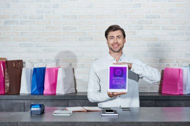Handsome young salesman holding digital tablet with shopping application and smiling at camera in shop stock vector