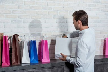 young salesman working with paper bags in shop