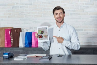 handsome young salesman pointing at digital tablet with ebay application and smiling at camera in store