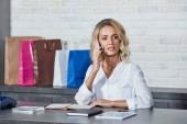 Fotografie atraktivní mladá žena mluví o smartphone a koukal při práci v obchodě