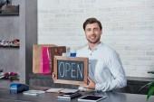 csinos fiatal eladó gazdaság jel megnyitása és mosolygós, a fényképezőgép-bolt