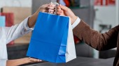 Fotografie cropped shot of seller and buyer holding shopping bags in store