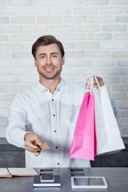 smiling young salesman holding paper bags and credit card in shop