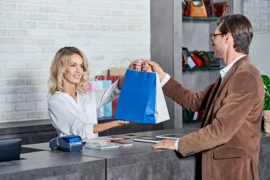 smiling young seller giving shopping bags to handsome customer in store