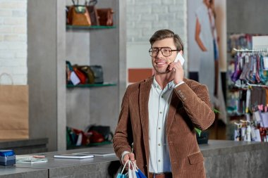 handsome smiling man in eyeglasses holding shopping bags and talking by smartphone in store