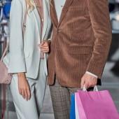 Oříznout záběr stylový pár se drží nákupní tašky v obchoďáku