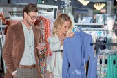 člověk pomocí smartphone zatímco usměvavá mladá žena výběr oblečení v obchodě