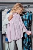 Fényképek vonzó nő gazdaság fogas divatos inget butik