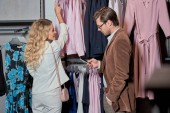 ember használ smartphone, miközben kiválasztja ruhákat bemutatóteremben nő