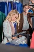 Fényképek fiatal nő, miközben unatkozik az ember áll mögötte a boutique ruházat kiválasztása