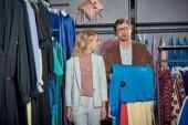 mladý pár výběr stylového oblečení v showroomu
