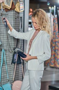 beautiful young woman choosing handbag in boutique
