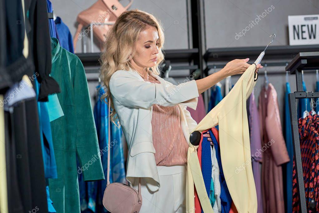 Beautiful young woman choosing clothes in fashion store