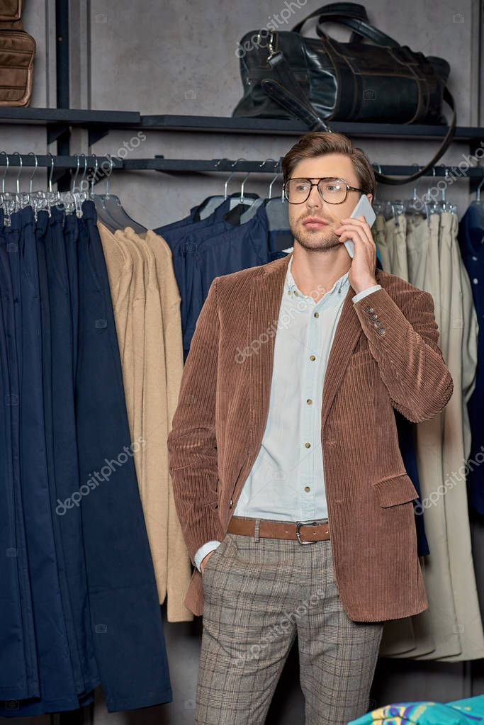 Handsome man talking by smartphone while shopping in boutique