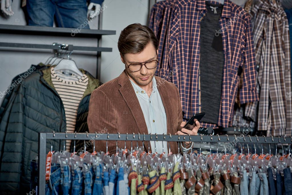 Handsome man in eyeglasses holding smartphone and choosing fashionable clothes in shop
