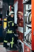 boční pohled na ženské hasič s hasicí přístroj na zpět uzavírací vůz na hasičské stanici