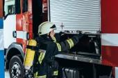 ženské hasič s hasicí přístroj na zpět uzavírací vůz na hasičské stanici