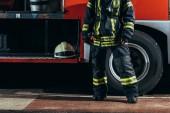 částečný pohled ženské hasič v ochranné jednotné stojící poblíž truck s helmou na hasičské stanici