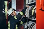 boční pohled na hasič v ochranné jednotných kontrolních zařízení v autě na hasičské stanici