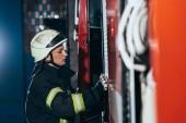 boční pohled na hasič v uniformě uzavírací vůz na hasiče