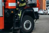 oříznutý snímek hasič v ohnivzdorné jednotné postavení na hasičské auto na ulici
