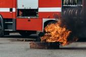 zblízka pohled na hořící plamen a hasičský vůz na ulici